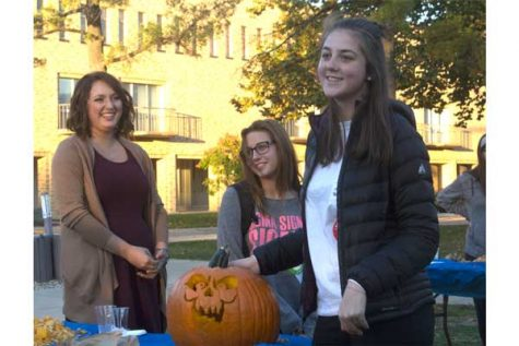 "Luiza Sobell, freshman psychology and marketing major, explains her team's pumkin design to Eastern president David Galssman and members of the crowd who helped Glassman pick her team's pumkin as the winner of 'Pumkin with the Pres,"" hosted by the Eastern student senate. Sobell said she is from Brazil, so she had never carved a pumkin before Monday. ""I've always liked the designs I've seen in movies and I wanted to do one,"" Sobell said."
