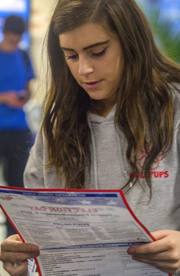 Ashley Dietzen, a freshman business administration major, looks at a flyer, which highlights the candidates running at the local and national level, polling locations and early voting information Monday in the Bridge Lounge of the Martin Luther King University Union.