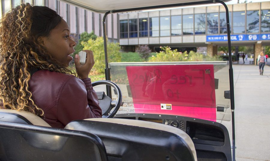 Trayshell Williams, a senior sociology major, uses a megaphone speaker to tell students to vote while she was driving a golf cart Monday in the Library Quad. Williams was also giving students rides to the Martin Luther King Jr. University, where they were able to register and vote.