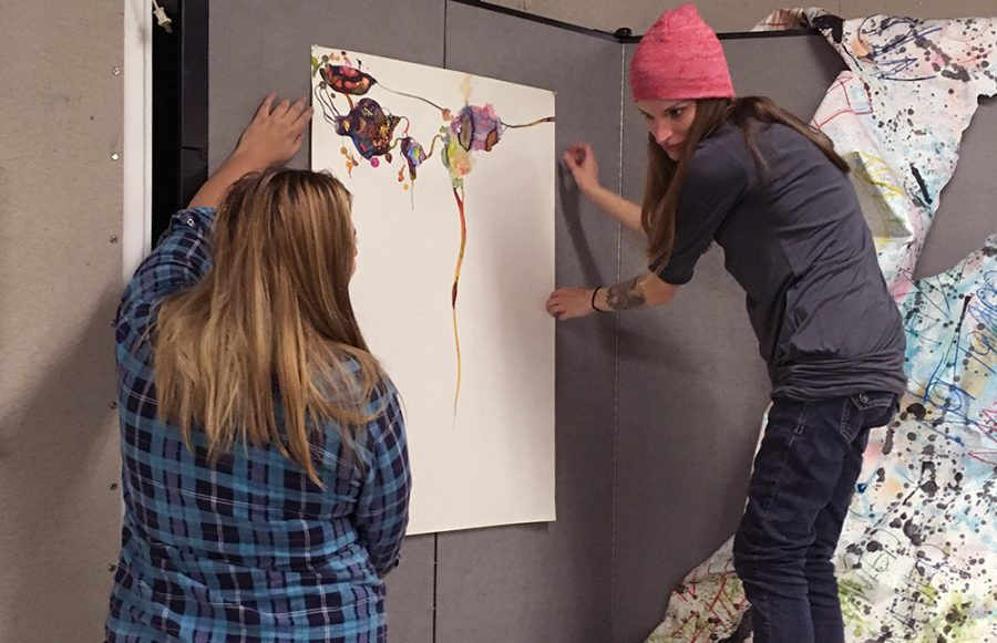 Sage Spencer and Alysia Klein hang art in preparation  for the No Pretense art show, which is to be held Wednesday in the Doudna Fine Arts Center.