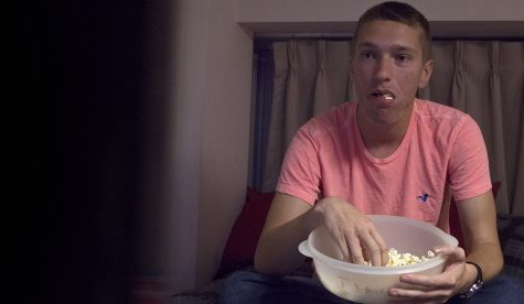 Alek McMath, a freshman marketing major, eats popcorn while watching Netflix in his friend's dorm Tuesday night. Netflix released nine new titles for December, compared to over 30 released last November.