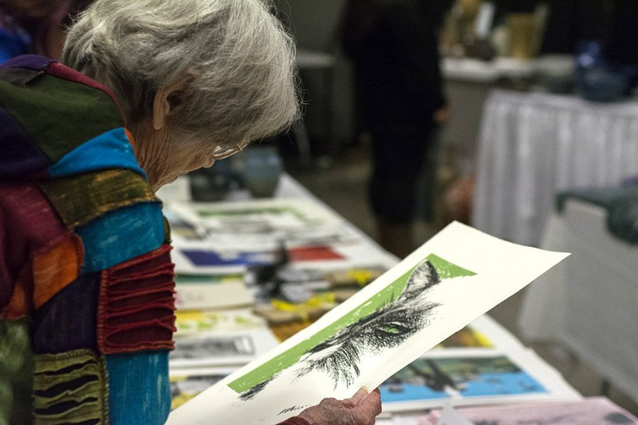 Carol Lynch of Charleston looks over art during the Holiday Art Sale at Doudna on Thursday. The sale, put on by the art department raises money for the undergraduate art department scholarship fund.
