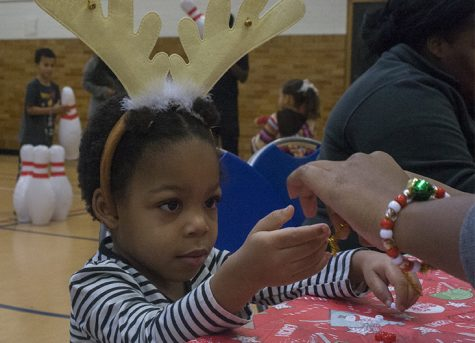 """Aiyana Goodson, 4, daughter of senior communication studies major LeLonna Goodson, creates jewelry at """"Breakfast with Santa"""" Saturday morning in the McAfee Gym. Though Goodson was originally making a bracelet, the students helping her joked that because she kept adding items to it, it would be more like a necklace, as the bracelet would be too big for her tiny wrist."""