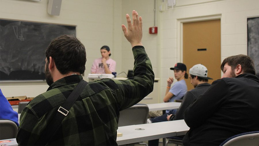 Ryan Naples applied engineering and technology major raises his hand during the weekly Construction Club meeting held on Tuesday in Klehm hall to discuss next weeks election nominations and need for club member recruitment. Jake Scarlati, applied engineering and technology major and vice president of the Construction Club led the meeting.