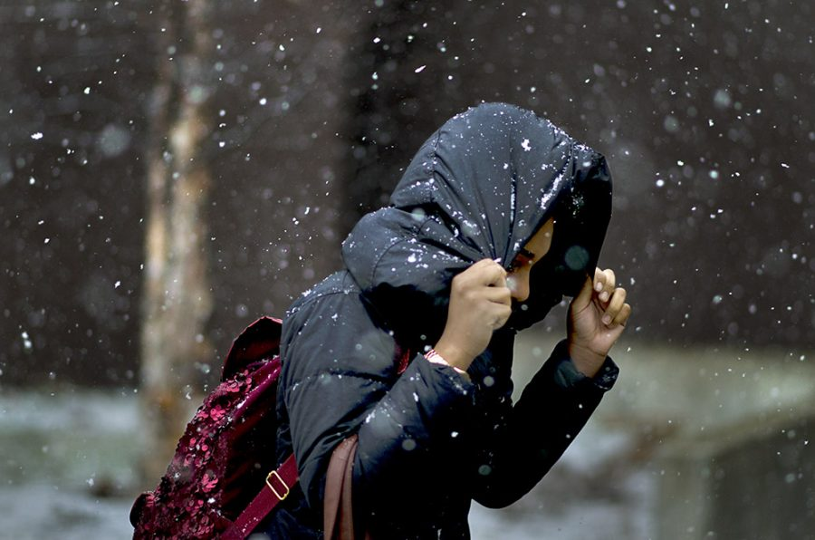 An Eastern student does her best to avoid the snow as she made her way to Doudna Fine Arts Center Wednesday.