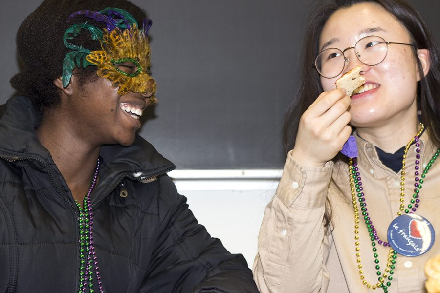 Anita+Saffa%2C+a+junior+economics+major%2C+and+Jane+Kim%2C+a+junior+exchange+student+from+South+Korea+snack+as+part+of+their+participation+in+The+Mardi+Gras+celebration+in+Coleman+hall.