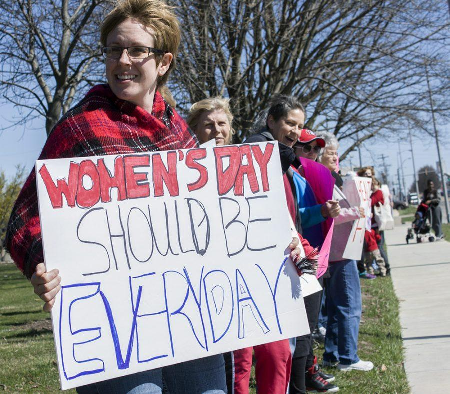 Jessica Mertz, a Charleston resident, holds a sign during the International Women's Day protest Wednesday along Lincoln Avenue.