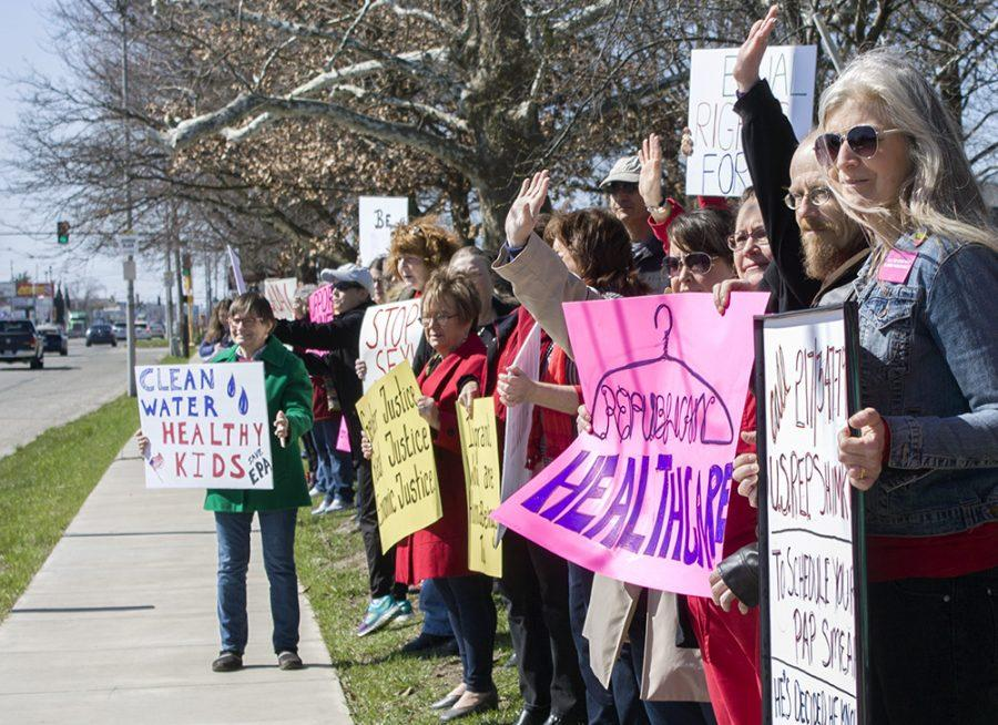Local activists, who were protesting a host of issues for International Women's Day, wave at a honking passerby Wednesday along Lincoln Avenue.