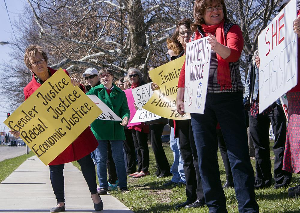 Local women hold up signs to protest inequality and show support for immigrants and other minorities during International Women's Day Wednesday along Lincoln Avenue.