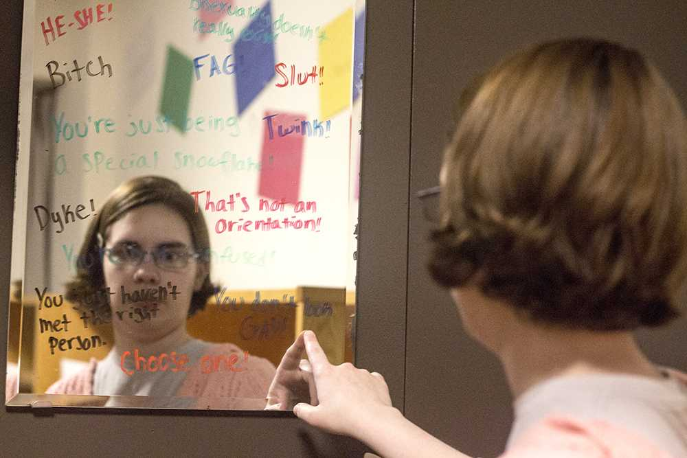 "Lee Harper, a senior pshychology major,stares into a mirror with derogatory phrases sorrounding the LGBT community. ""As an asexual person I get the 'you just haven't met the right person yet.' People just don't understand,"" says Harper."