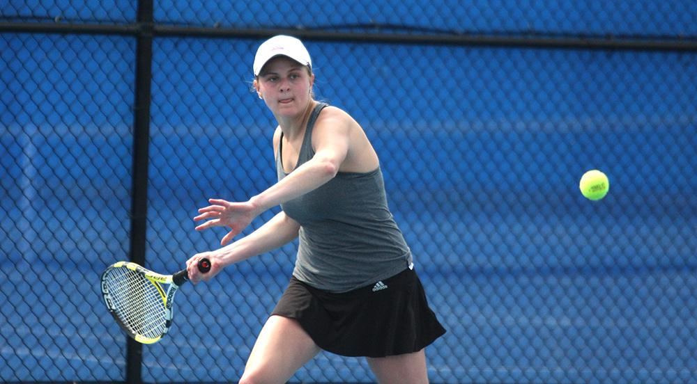 Kelly Iden returns the ball in her singles match Friday at the Darling Courts. Iden won her singles match 7-5, 7-6 and (7-5).