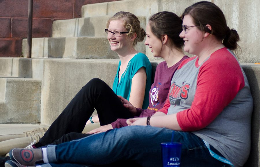 Justin Brown | The Daily Eastern News Sophomore Kayley LaGrou, left, a mid-level education major, junior Hannah Blanck, center, an elementary education major and junior Danielle Stelsel a special education major sit on the Doudna steps. The three took advantage of the warm temperatures Monday to