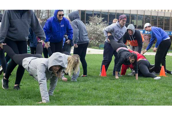 Members from several sororities and fraternities team up and compete in a wheel burrow relay Thursday during the Greek Week Unity Relay Races, one of the many events happening during Greek Week 2017.
