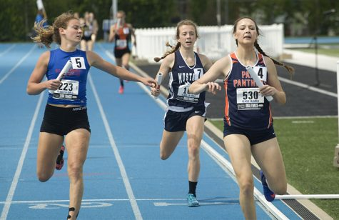 Kristin Slaughter (left), a senior from St. Anthony High School races with Bree Rochkes (right) from Pana High School and another competitor in the preliminary round on Thursday during the 4x400 meter relay.