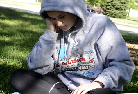 """Ellie Knepper, a rising senior from Sandwich Community High School in Sandwich, sits across from Andrews Hall Monday and reads from her phone during the American Legion Auxiliary Illinois Girls State. """"It's cool staying here,"""" she said, referring to living on a college campus and getting a feel for what it is like."""