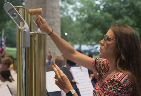 Megan McDevitt, a choir teacher at Charleston Middle School, plays the chimes during the Charleston Community Band concert Thursday at Kiwanis Park.