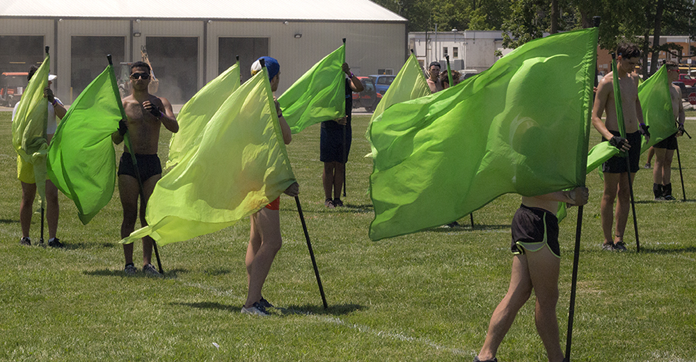 Members from the Cavaliers' color guard practice spinning their flags Monday afternoon near O'Brien Stadium.