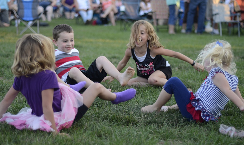 The great-grandchildren of the Farmer of the Year play Ring-Around the Rosie Monday night during the Charleston's Red, White and Blue Days celebration at Morton Park. The kids were there with their family to watch the Chris Lane concert.