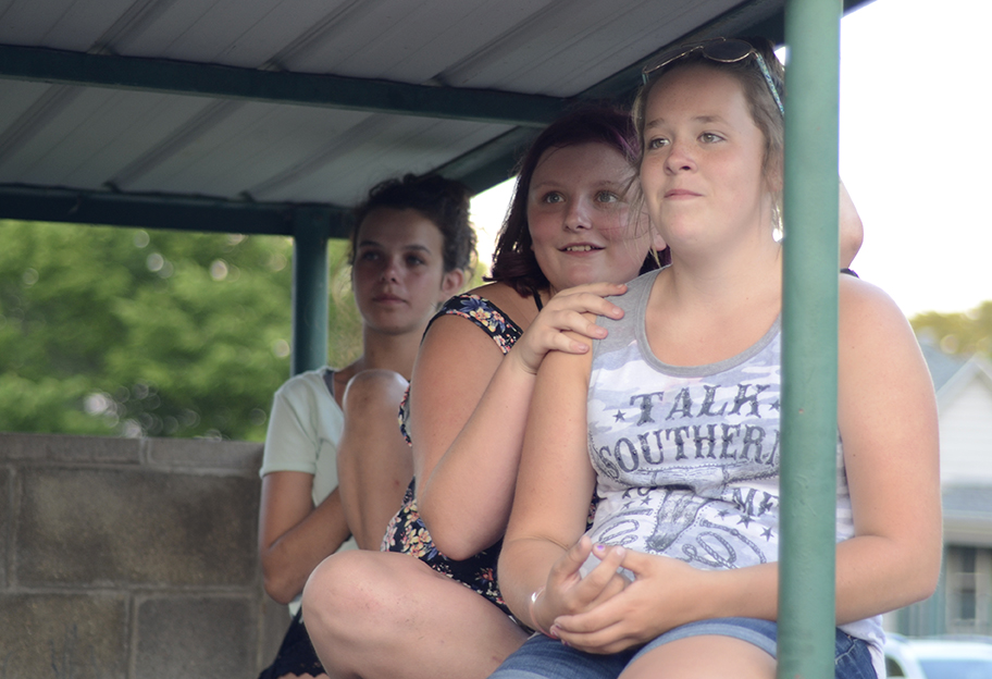 Kaylyn Doyle, Kallista Buckler and Maddi Bryant sit on top of a ledge connected to the dugout at Morton Park Monday night in order to get a better view of the Chris Lane concert during Charleston's Red, White and Blue Days.