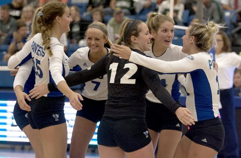 Freshman Laurel Bailey(15), junior Taylor Smith(7), redshirt sophomores Anne Hughes(12) and Gina Furlin(14), and senior Maria Brown(13) celebrate a point in their match against Green Bay Friday in Lantz Arena. The Panthers lost the match, but won both matches on Saturday against Memphis and Bradley.