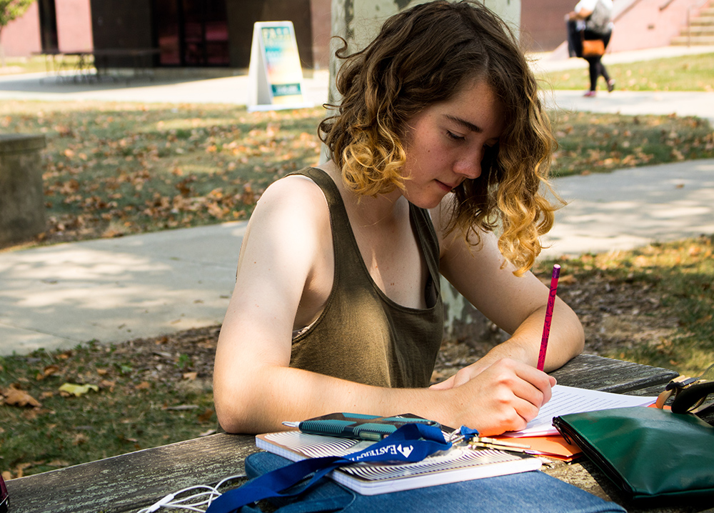 "Amanda Kiessling,a sophomore foreign language major, edits papers for her creative writing class in the Library Quad Sunday afternoon. ""I love being able to communicate with people whose native language isn't English, and learning about cultures in the world."" Kiessling said."
