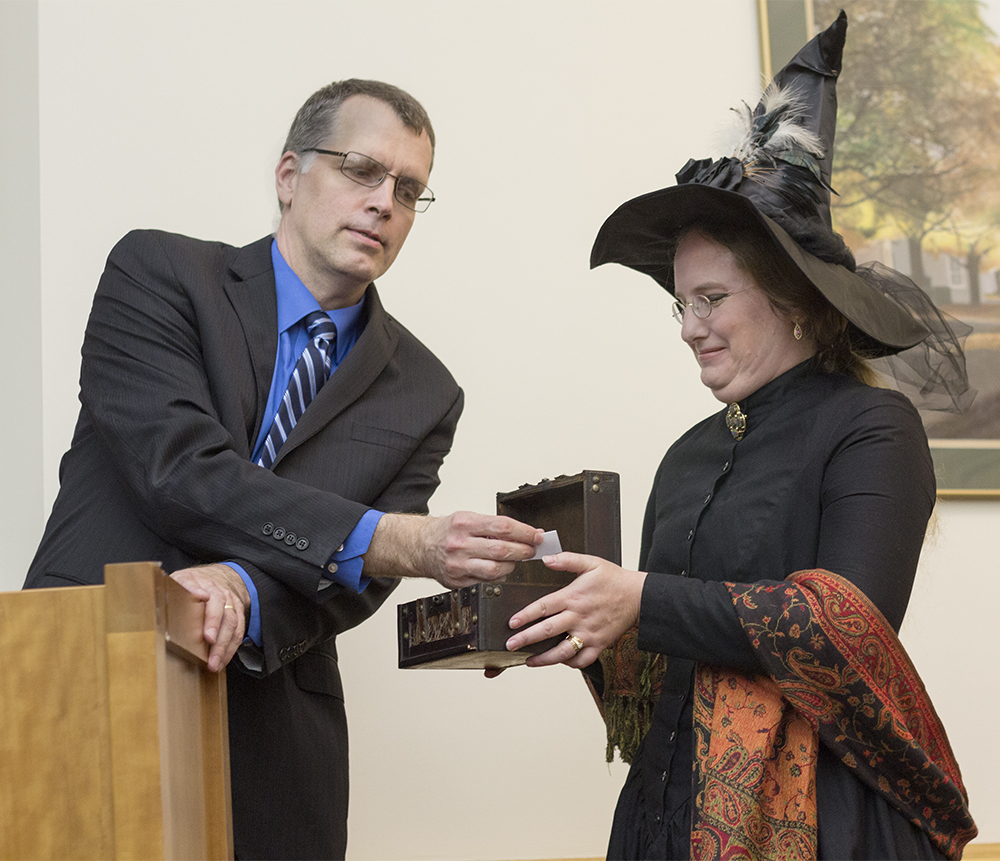 "Bradley Tolppanen, interim dean of Library Services, draws a name to win a scarf during the opening reception to the Harry Potter Exhibit ""Twenty Years of Harry Potter: Celebrating a Phenomenon."" Stacey Knight-Davis, head of Library Technology Services, dressed as Professor McGonagall from the Harry Potter series."