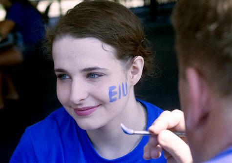 Angelina Loparco, a secondary education student here at Eastern, gets the EIU letters painted on her cheek Saturday in the walkway lounge at the Martin Luther King Jr. University Union. Angelina is showing her school spirit with a smile.