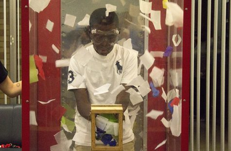 Jalon Emanuel, 13, grabs paper at the cash cube for a chance to win a prize at FUNfest in the Martin Luther King Jr. University Union on Saturday night. Emanuel came to visit his sister for Family Weekend. He won a $5 gift card for Steak 'n Shake.