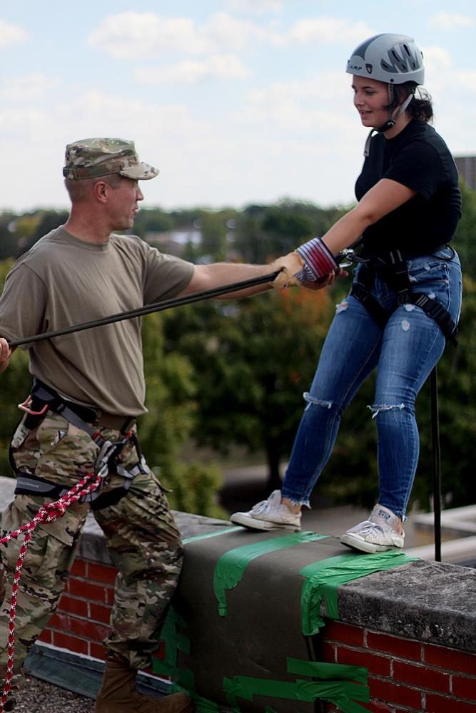Major Roy Waldhoff,a rappel master, encourages Ruth McMullen, a freshman JROTC student from Richland County High School, who was afraid to rappel off the side of Klehm Hall Friday afternoon during the ROTC rappelling training event.