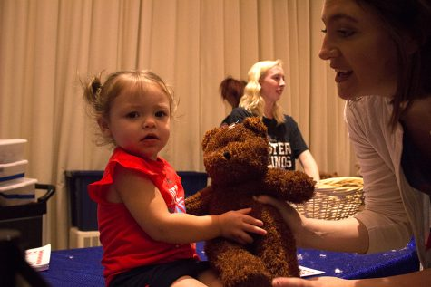 Grace Lee Probus, 2, grabs a bear from her mom Heather Probus at the bear stuffing station which was part of FUNfest at Family Weekend on Saturday night. They traveled from Lovington to visit Heather Probus' cousin who is an Eastern student.