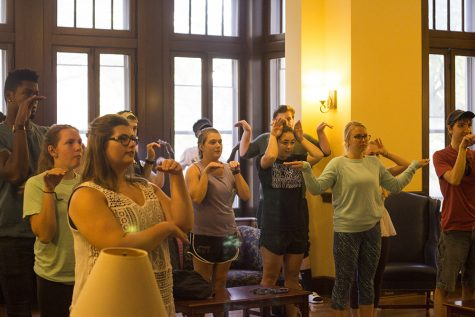 """Students warm up for the """"EIU Go"""" event at the Pemberton Great Room. The gestures they are making are related to the four houses from the Harry Potter book and movie series."""