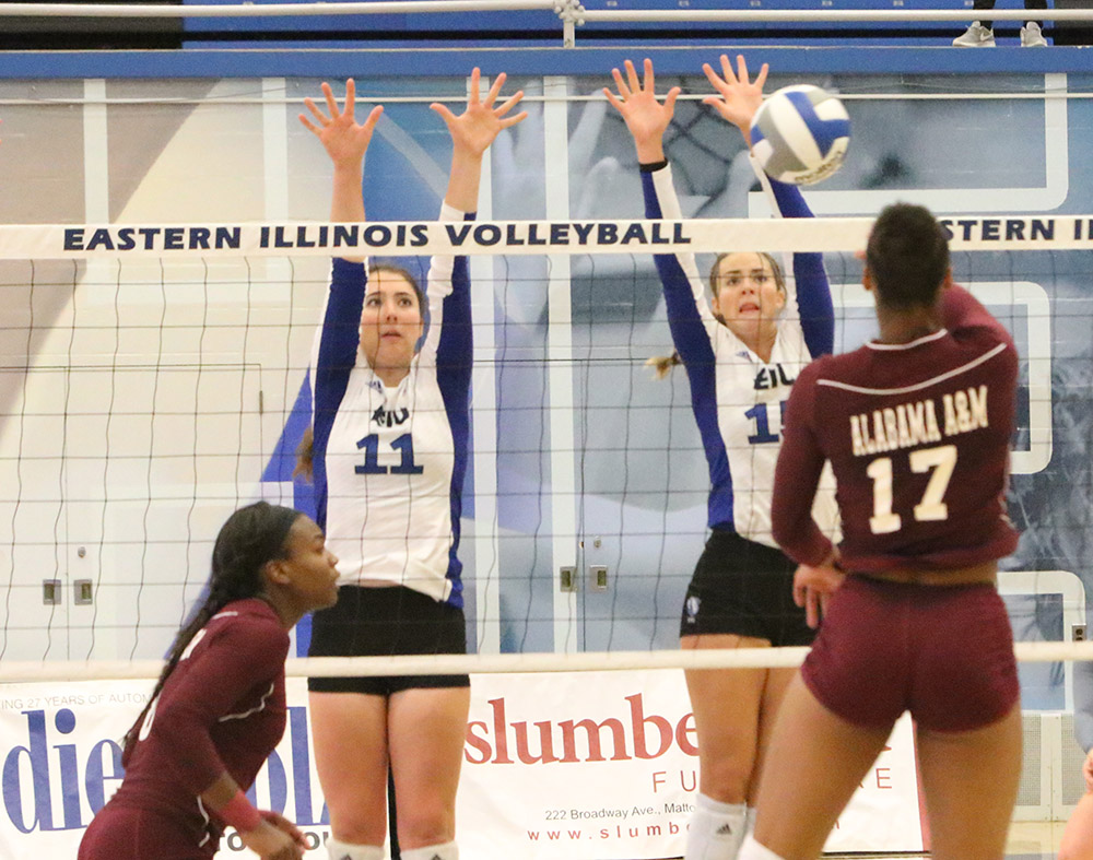 Eastern's Abby Knight and Laurel Bailey jump up over the net to block a shot by an opponent from Alabama A&M on September 8th at Lantz Arena. Eastern won the match three sets to 0.