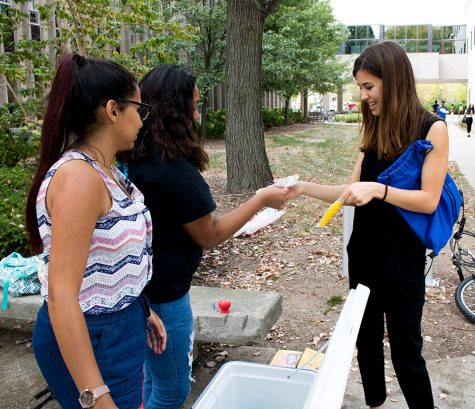Jordan Boyer | The Daily Eastern News Melissa Martinez, (left), a junior chemistry major and Blanca Aragon, (middle) a senior community health major, serve paletas, or popsicles, to Pamela Padilla, a sophomore Spanish education major, outside Coleman Hal Wednesday afternoon. Martinez and Aragon are both part of the women's empowerment registered student organization Esperanza. Esperanza raised just under $100 at the end of the sale. The money is going to help them run events in the future.