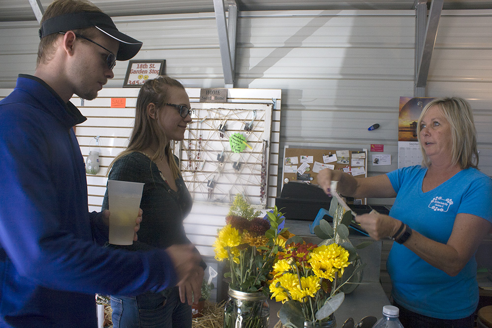 Sharon+Hunter%2C+owner+of+18th+St.+Garden+Stop%2C+sells+flowers+to+a+couple+of+customers+at+the+18th+Street+Fall+Festival+on+Saturday+afternoon.%0AHunter+said+the+business+was+%E2%80%9Csuper+busy%E2%80%9D+at+the+festival%2C+and+it+is+exciting+to+see+people+supporting+local+businesses.
