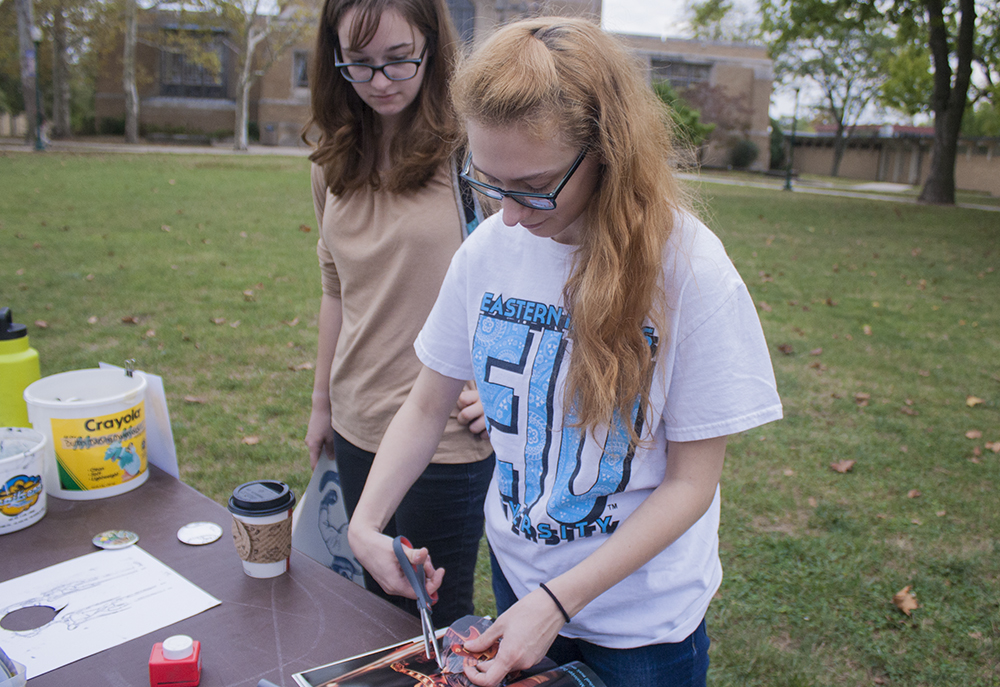 "Senior sociology major Lauren Eberle watches as her roomate and Art Association member Clair Gentry creates a button for the first time. ""It's a really personalized conceot to where you can just walk up and pick a very personalized image,"" Gentry said."