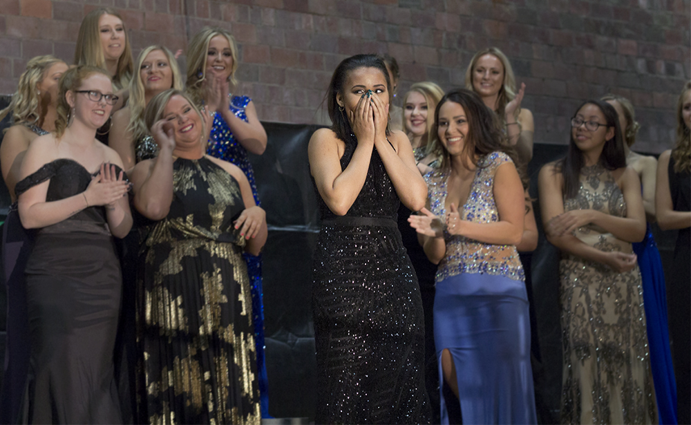Allison Oates, representative of Lincoln Hall and the NACWC, approaches center stage to receive her crown at the coronation event Monday evening.