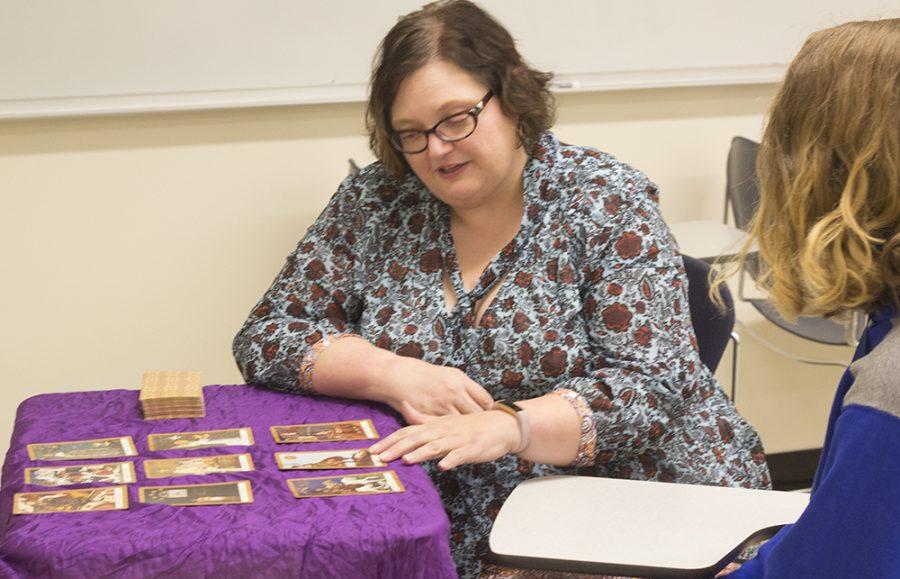 English club adviser Angela Vietto explains tarot card to Amanda kiessling,sophmore Foreign language major. Amanda said she is excited because she to play tarot card at last.