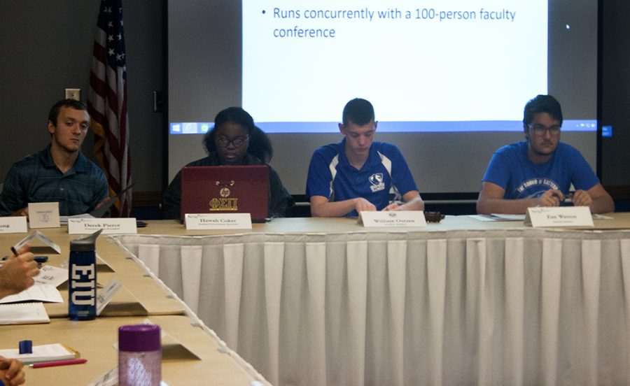 Derek Pierce (far left), Hawah Abdulrasaq Coker (middle left), William Outzen (middle right) and Ean Watson (far right) listen to a presentation during the Student Senate meeting Wednesday night in the Arcola/Tuscola Room of the Martin Luther King Jr. University Union.