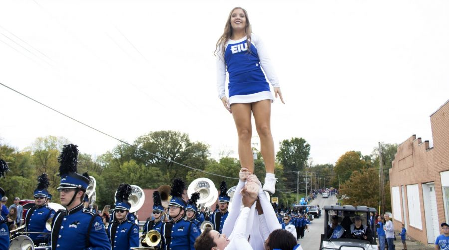 An Eastern cheerleader is held up along side the marching band at the homecoming parade on Seventh street.