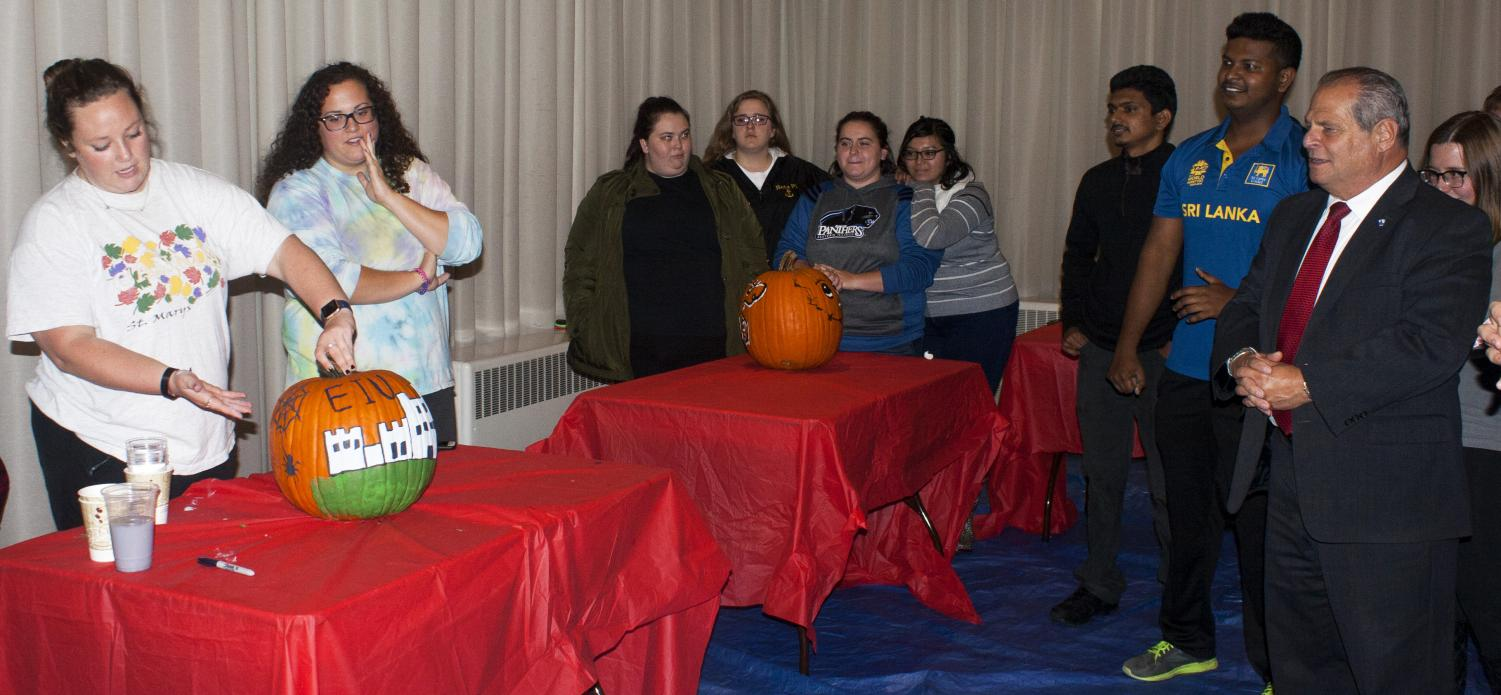 "Students from Sigma Sigma Sigma (left) showcase their pumpkin to Eastern President David Glassman (right) and other students during ""Pumpkins with the Prez"" at the University Ballroom located at the Martin Luther King Jr. University Union Monday night."