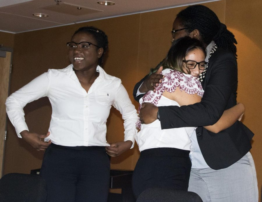 Claude Abdoulaye- Pedila (left) a psychology major, smiles while Catherine Polydore a proffesor of counseling and student development hugs Yesenia Murato a sophmore sociology major after the Immigration Panel at Doudna hall Monday night.