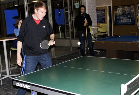 Jordan Boyer | The Daily Eastern News Matt Williams a senior buisness managment major plays ping pong at the Pizza, Pool, and Police event at Taylor Hall Tuesday night.