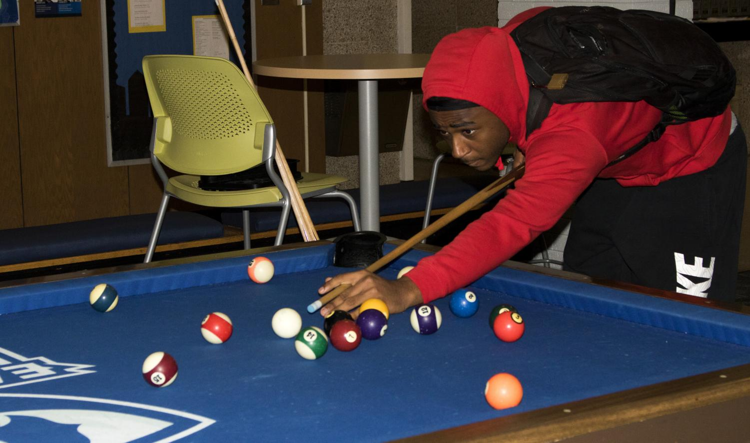 Jordan Parks, a freshman pre-med major, plays pool at the Pizza, Pool and Police event in Taylor Hall Tuesday night.