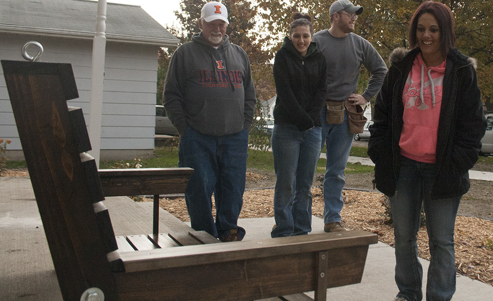 Mattoon resident Aisha Crowe, standing by her daughter and a couple of volunteers from Habitat for Humanity, admires the porch swing made by Eastern's Construction Club. The porch swing was presented to Crowe on Saturday morning.