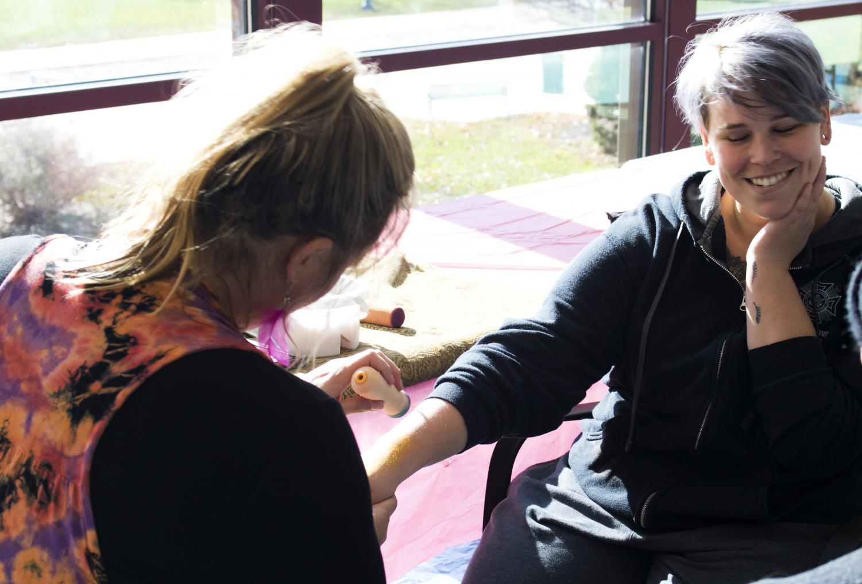 Face painter Britt Dodd paints senior special education major Holly Sosamon's arm at the the University Board's