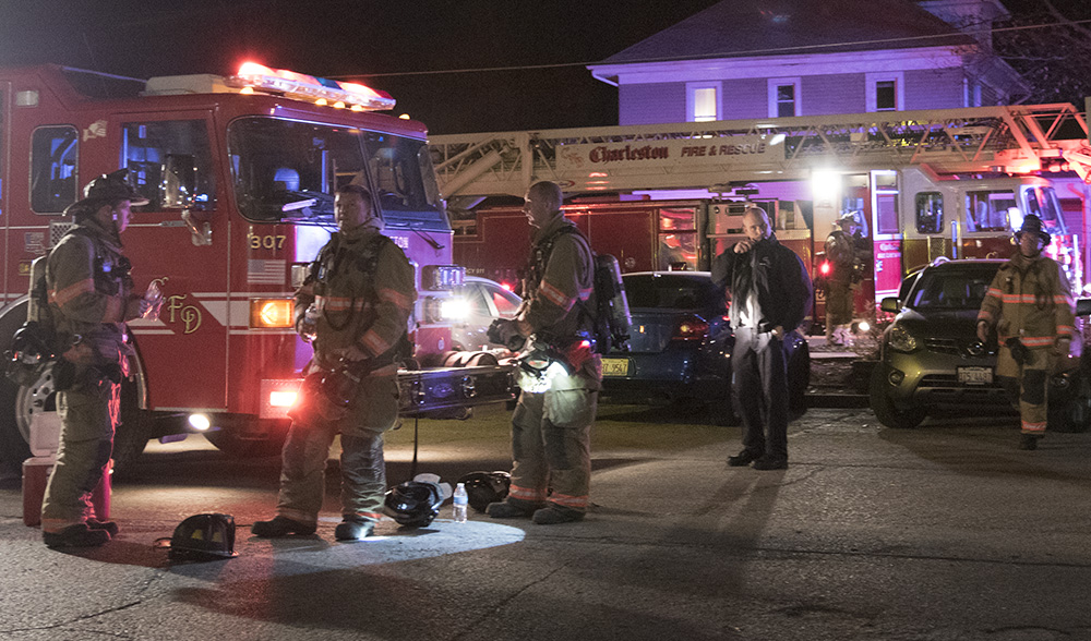 Firefighters regroup in the parking lot of Douglas Hall Wednesday night after a fire broke out in the building's attic.