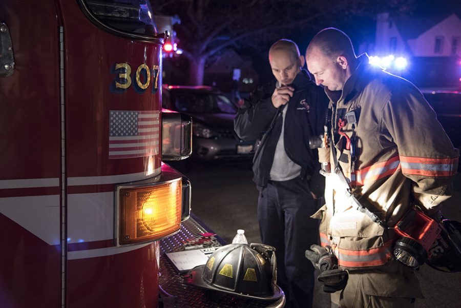 Steve Bennett (left), chief of the Charleston Fire Department, discusses the situation with a firefighter in the parking lot of Douglas Hall Wednesday night after the building's attic caught on fire.