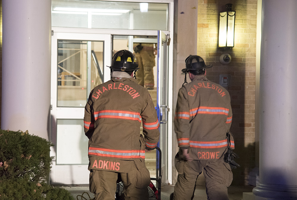 Two firefighters enter Douglas Hall Wednesday night after a fire broke out in the building's attic.