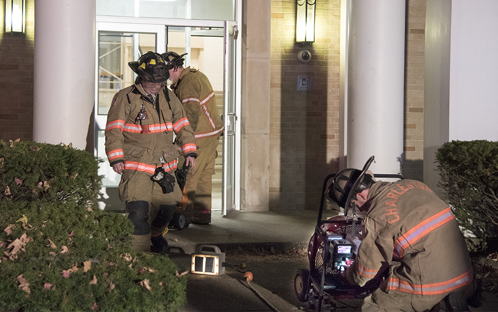 Firefighters set up fans to air out the smoke from Douglas Hall Wednesday night after a fire broke out in the building's attic.