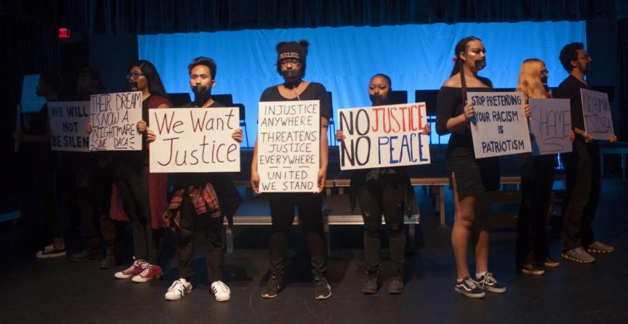 "Travis Moody | The Daily Eastern News The company of ""Serenade of the Silent Soul"" holds up signs relating to issues concerning social justice. The black tape on their mouth symbolizes the silent soul of marginalized groups."